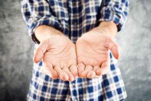 Cupped hands of a man hopefully held up. Cupped hands asking for help or charity
