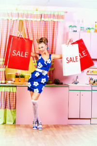 Fashionable pin-up girl standing with shopping bags on a pink kitchen. Retro style. Sale.
