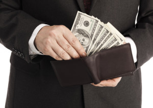 Businessman with wallet full of one hundred dollar bills